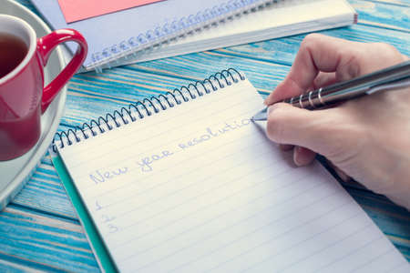 female hand writing about new year resolutions in a notebook Stok Fotoğraf