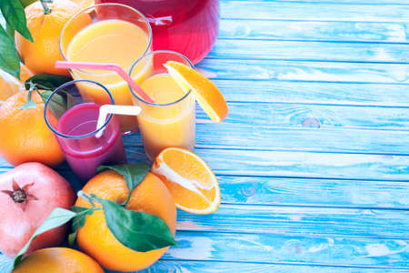 freshly squeezed orange and pomegranate juices with oranges and pomegranate fruit on a blue wooden background