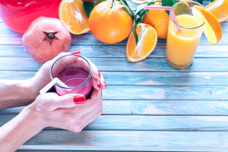 freshly squeezed pomegranate juice in a women's hands with oranges and pomegranate fruit on a blue wooden background 版權商用圖片 - 143975150