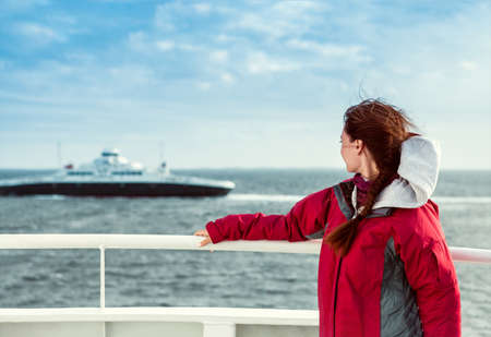 the girl in a red jacket on the ferryboat looks towards the sea, where the liner floats Stok Fotoğraf