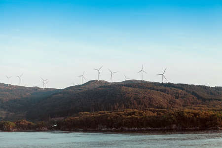 Alternative Energy Wind Turbines in the mountains on a sea and blue sky background Stok Fotoğraf