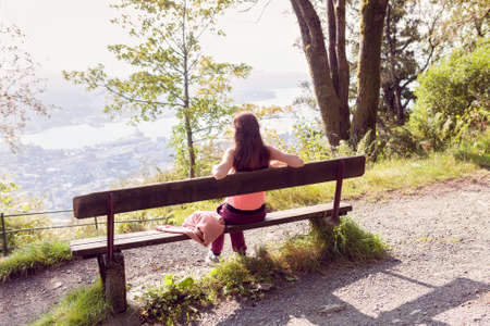 the girl sits on a bench in the forest, her back to the camera and a panorama of the city opens in front of her 版權商用圖片 - 145663881