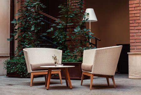 A place to relax with armchairs made of straw and torchere in the yard against the background of the house