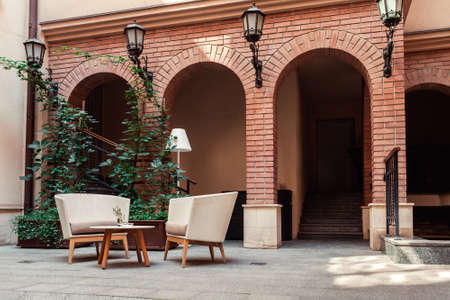 A place to relax with armchairs made of straw and torchere in the yard against the background of brick arches 免版税图像
