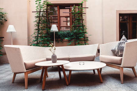 A place to relax with armchairs and sofa made ​​of straw in the yard against the background of the house