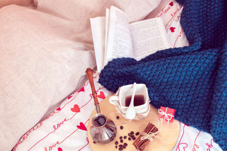 Cozy still life of breakfast in bed for St.Valentine's Day. Coffee with small gift and plaid with book on a background in isolation period