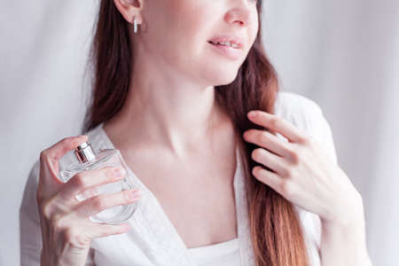 girl in a white dress sprays herself perfume on her neck