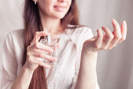 girl in a white dress sprays herself perfume on her wrist Foto de archivo