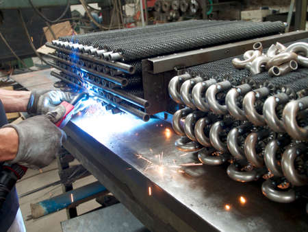 blue flame: WELDING METALLIC TUBES WITH BLUE FLAME Stock Photo
