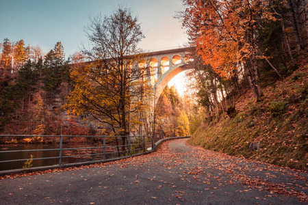 Bridge over River at Sunset with Autumn Foliage