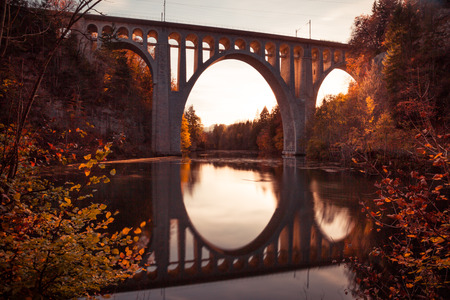 Bridge Reflecting in River at Sunset with Autumn Foliage