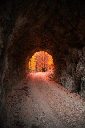 Stone Carved Tunnel and Red Sunset Light opening on Autumn Foliage