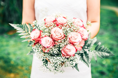 Newly Wed Woman Holding her Bridal Bouquet in a Green Garden