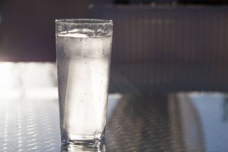 Tall Icy Cold Glass of Water with Water Drops Reflecting on Glass Table Stock Photo