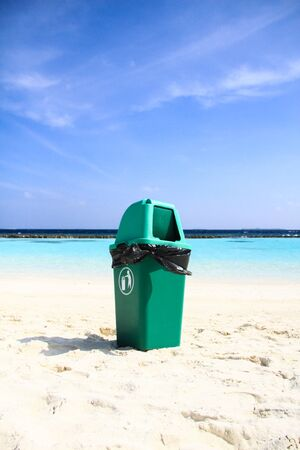 Green Plastic Bin on Clean Sandy Tropical Beach after Recycling Waste