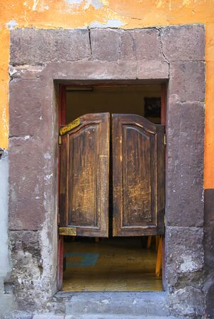 Old Mexican Battered Wooden Saloon Style Door with Cracked Wall