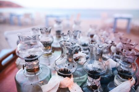 Old Oil Glass Lamps with DIY fixes gathered on Table on Greek Beach at Sunset