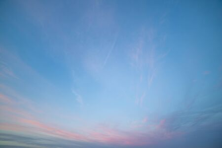 Partially Cloudy Pastel Pink and Purple Dusk Light with Blue Sky