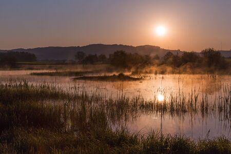 Misty Golden Sunrise Reflecting over Lake in Spring