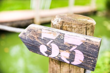 Number Thirty-three Hand Painted on Wooden Post in Outdoors Circuit Stock Photo