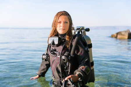 Female Scuba Diving Instructor Standing in Water Wearing a Dry Suit, a Twin Tank and Holding Fins