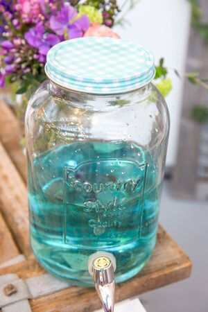 Vintage Country Style Glass Jar with White and Blue Lid Containing Turquoise Drink Stock Photo