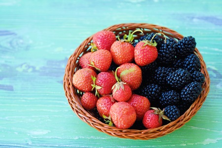 Blackberries and strawberries from the garden on a wooden background