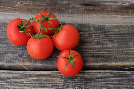 Red ripe tomatoes on a wooden background view