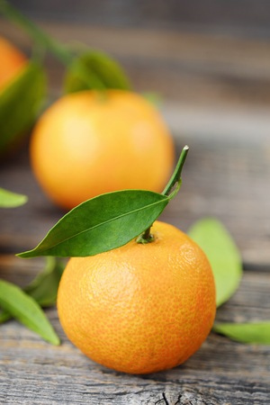 desk: Fresh tasty tangerines with leaves on a wooden table