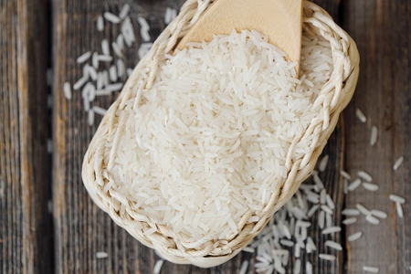 White long grain rice on a wooden spoon