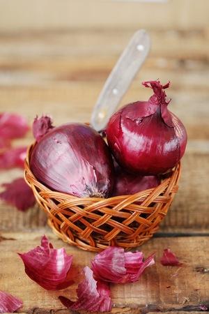 Cebolla roja fresca y cuchillo sobre la mesa