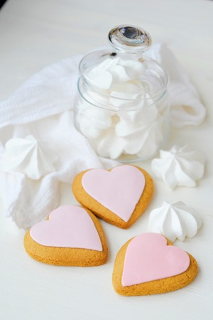 White fresh meringues and cookies in a glass jar