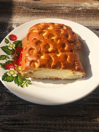 Tasty bun with cottage cheese on a wooden table
