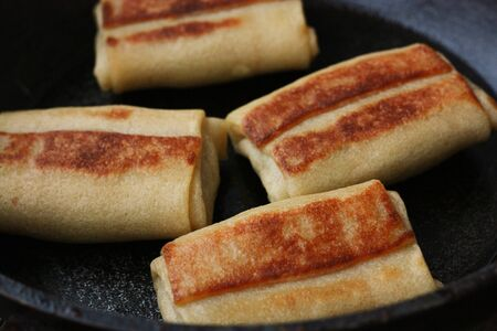 Pancakes with meat in a pan close up
