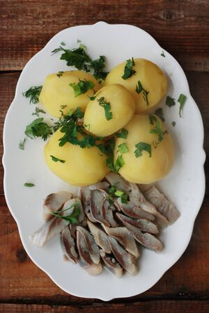 Delicious potatoes with dill and herring for dinner Stock Photo