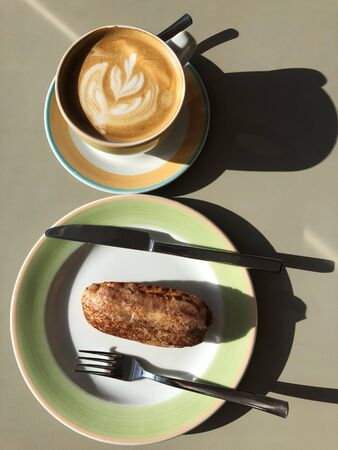 Fresh coffee and cocoa Eclair on the table