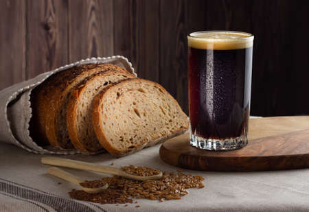 Kvass with rye wholegrain bread on wooden background. Front view.