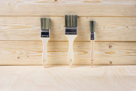 New paint brushes and unpainted pine boards. Home renovation or DIY concept. Banco de Imagens