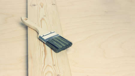 New paint brushes on unpainted pine board on wooden background. Home renovation or DIY concept.