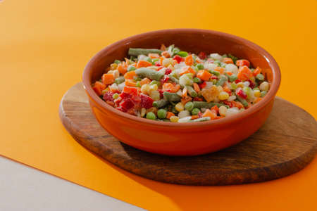 Mix of frozen vegetables in a ceramic baking dish on wooden board. Healthy veagan food.