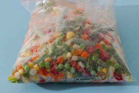 Mix of homemade organic frozen vegetables in a plastic bag: paprika, carrot, green beans, tomato and green pea. Healthy and vegan food.