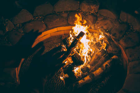 He warms his hands on the fire on a summer evening. He warms his hands on the fire on a summer evening. Focus on the fire.