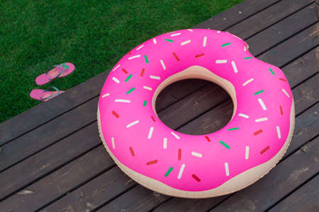 The inflatable circle in the form of a donut lies on a wooden pier. to lie on the lawn. Summer, beach season.