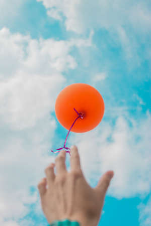A woman's hand let go of the orange helium ball, it flies to the sky. The air ball flew away 写真素材