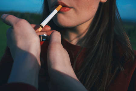 The girl is smoking a cigarette. Female hands hold a lighter.