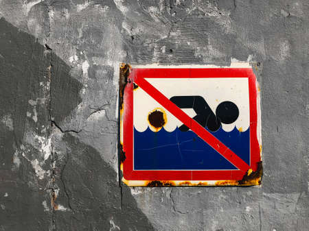 Bathing is prohibited. A rusty sign with a swimmer on the background of an old concrete wall. Ban on swimming red blue danger sign.