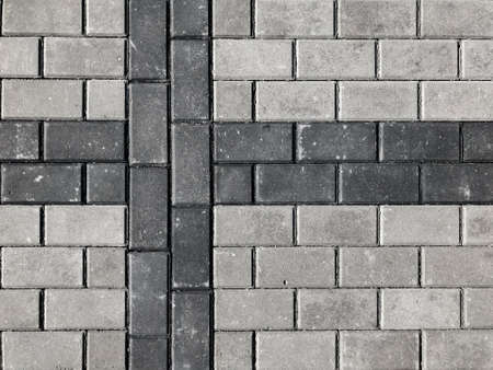 Texture of road tiles. Grey tiles without a pattern. Drawing a black cross on a gray tile. 写真素材