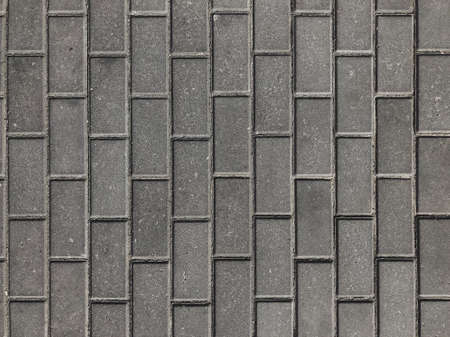 Texture of road tiles. Grey tiles without a pattern. Drawing a black cross on a gray tile. Stock Photo