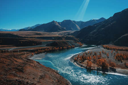 Autumn landscape with mountains and river. Blue sky