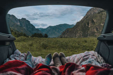 Summer landscape with mountains, the view from the car. Legs of resting people on nature. Sleeper in the car. Travelers are in the car and look at the mountains.
